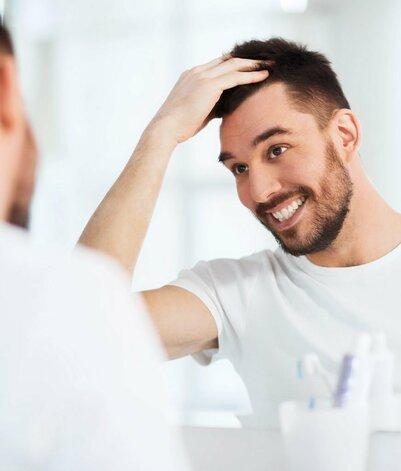 Man-smiling-face-to-mirror